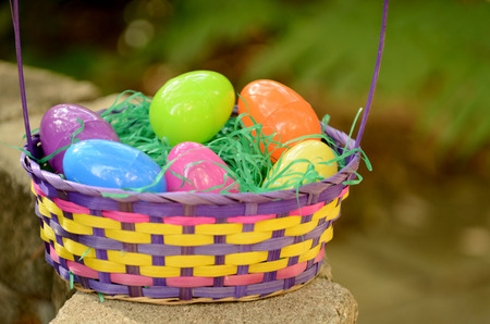 colorful easter basket with plastic eggs and green grass  photo