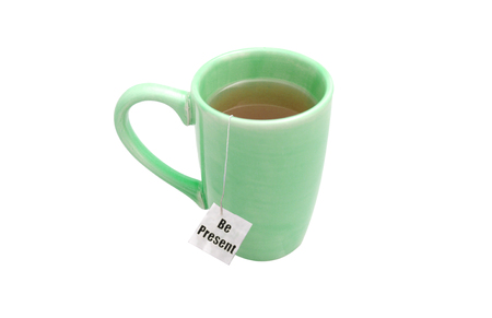 be present concept with message on tea bag