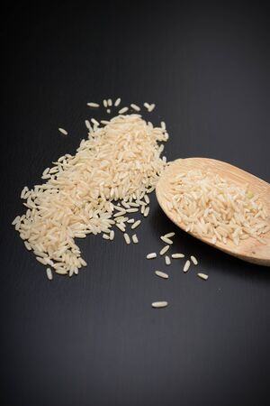 country store: raw brown rice with a wooden spoon Stock Photo