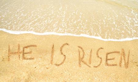 comunicación escrita: Ha resucitado escrito en la arena para la Pascua en la costa