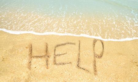 comunicación escrita: concepto sos con la ayuda escrito en la arena en la costa Foto de archivo