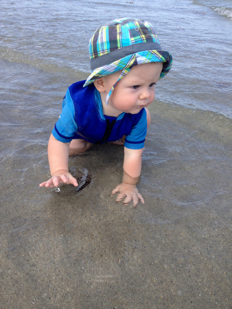 8 9 months: Baby crawling through ocean water at the beach wearing a hat and a wetsuit Stock Photo