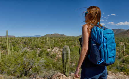 tuscon: desert hike with hair blowing in the wind while looking at the beautiful landscape