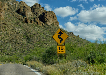 tuscon: Drive with caution at 15 miles per hour because of curves in the desert mountain road Stock Photo