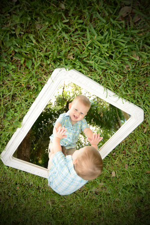 8 9 months: Young infant male child looking at self in mirror Stock Photo