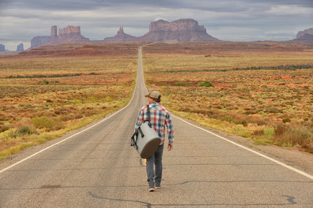 loner: Wanderer or loner in Monument Valley walking down an empty road Stock Photo
