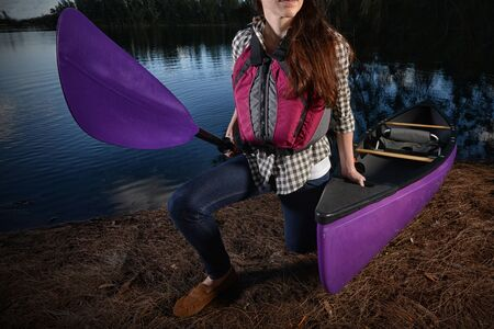 woman kayaker and a purple kayak at lake in the fall with a plaid shirt and jean Фото со стока