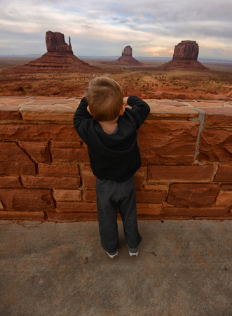 native american baby: Toddler travel concept with child overlooking the Monument Valley desert landscape Stock Photo