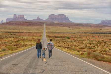 Family travel and walking down road to Monument Valley while holding hands with a child