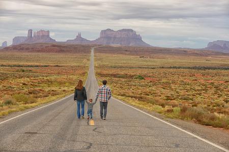 Viajes en familia y caminando por la carretera a Monument Valley, mientras que de la mano con un niño Foto de archivo - 47349404