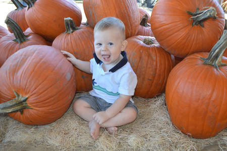 10 month: Baby at pumpkin patch on a warm autumn day Stock Photo
