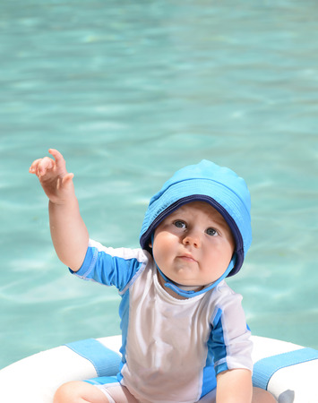 8 9 months: Young infant at pool with life preserver or lifesaver for a water safety concept