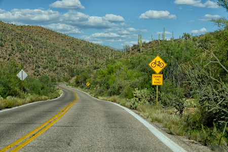 tuscon: share the road with bicycles sign on empty road in arizona Stock Photo