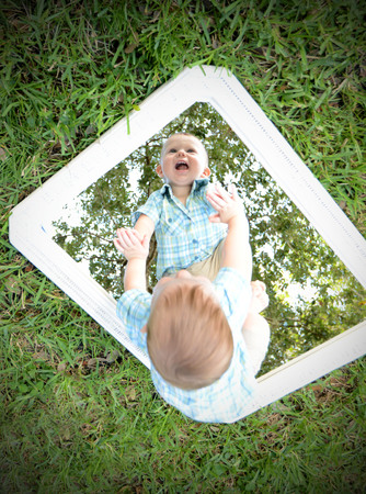 recognizes: Young baby looking at self in mirror while smiling because he recognizes himself