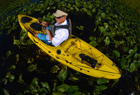 lily pads: man kayak fishing in lily pads in yellow kayak