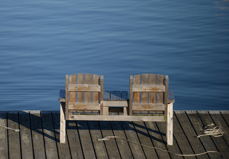 empty bench: Empty bench overlooking the water in a calm, tranquil scene
