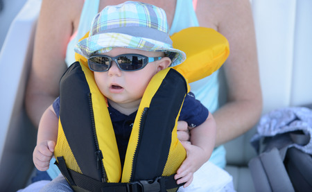 8 9 months: Mother holding baby with lifejacket on that needs to be zipped up with sunglasses and hat Stock Photo