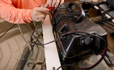 man charging boat battery by connecting the wires