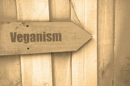 veganism: arrow sign with the word veganism on wood