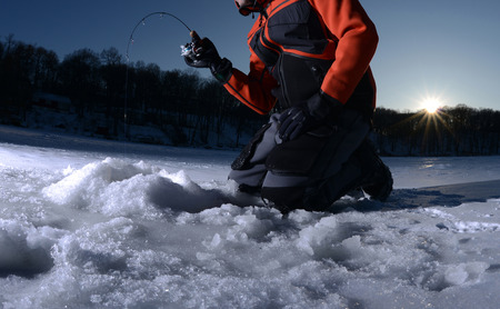 Man ice fishing on a lake in winter