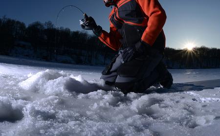 Man vissen op het ijs op een meer in de winter