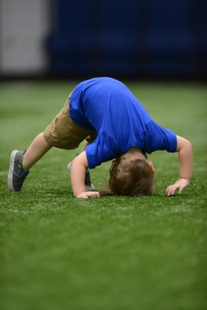 petit enfant en bas âge mignon essayer de faire barattage ou un saut périlleux à la gymnastique