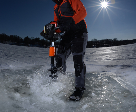 freshwater: man ice fishing and drilling hole in the ice of a frozen lake