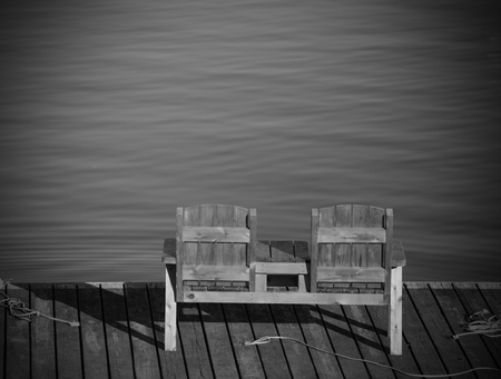 empty bench: Empty bench overlooking the water in a tranquil scene Stock Photo