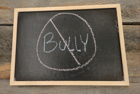 No bullying written in chalk on a chalkboard on a rustic background