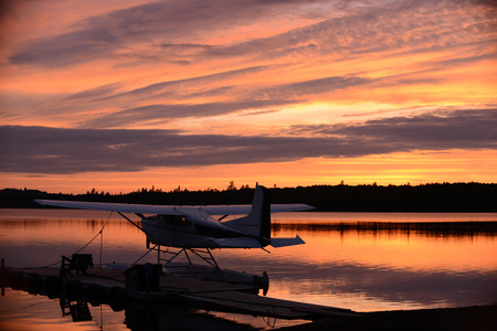 retreat: Sunset at an outdoor retreat with a seaplane on a lake near a dock