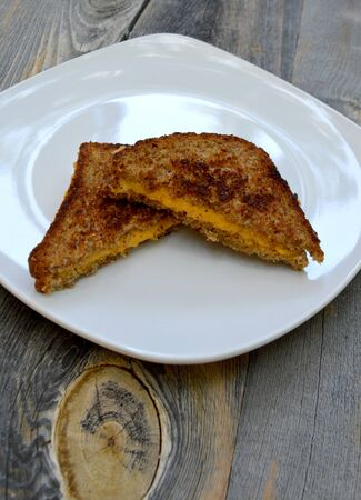 comfort food: Vegan comfort food with a vegan grilled cheese sandwich on a wooden background Stock Photo