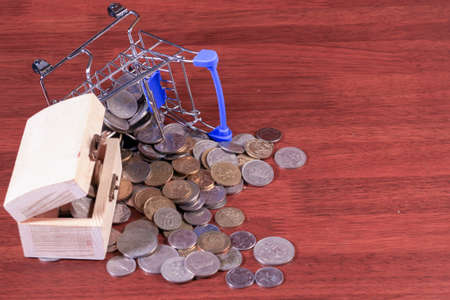 Miniature shopping cart full of coins on a wooden background- payments, investments and commerce concept