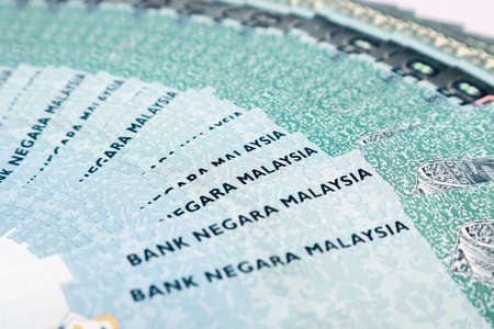Malaysia Currency (MYR): Stack of Ringgit Malaysia bank note. There is a fifty ringgit malaysia scattered on the white backdrop