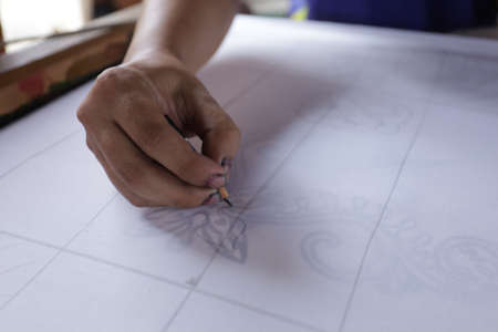 Unidentified local woman/ men sketching freehand with canting tools and hot wax to create a traditional Batik Canting at workshop.