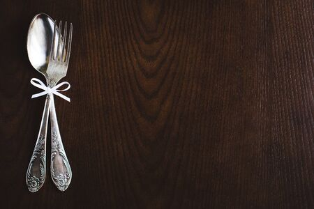 tied together: Fork and spoon tied together with a bow-knot