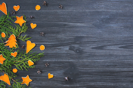 arborvitae: Christmas background with cones, branches arborvitae and orange skin figures Stock Photo
