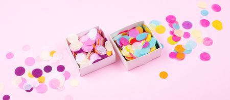 Two boxes with confetti on pink background.