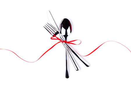 Fork, spoon and knife tied with red ribbon. Isolated on white.