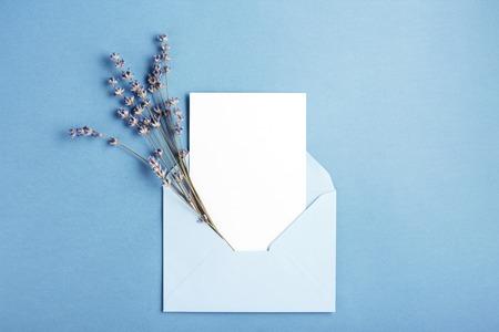 Mockup met kaart en lavendel in blauwe envelop. Bovenaanzicht. Stockfoto