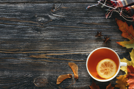 Autumn hot tea with lemon decorated yellow and red leaves, and checkered scarf on wooden table. Top view with copy space. 스톡 콘텐츠