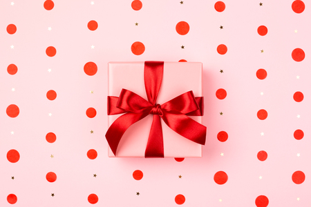 Pink gift box with red bow on pink background with red polka dots and sparkles. Holiday card concept.