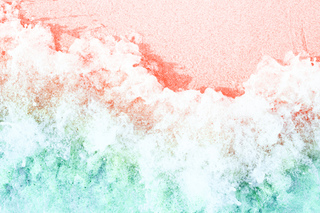 Soft waves with foam on sandy beach toned in trendy colors of the year 2019. Living Coral and Limpet Shell.