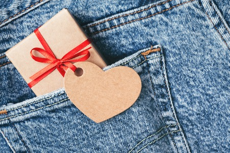 Kraft gift box with red bow and tag in shape of heart sticking out of blue jeans pocket. Valentines day card.