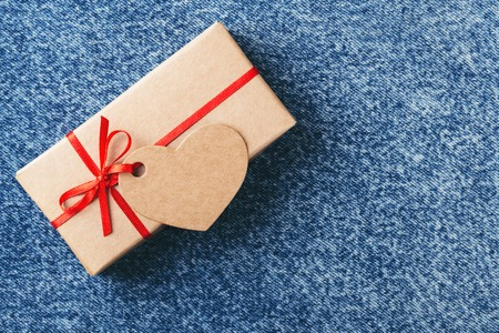 Kraft gift box with red bow and tag in shape of heart on blue jeans. Valentines day card.