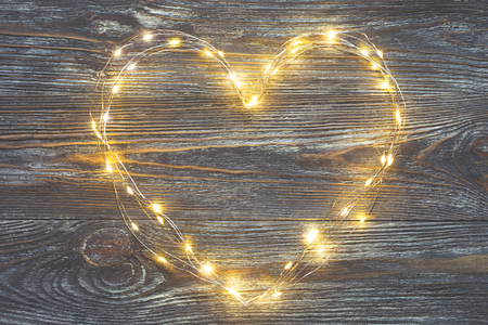Garland lights in the shape of heart on a rustic wooden table. Concept of Love and Valentines day