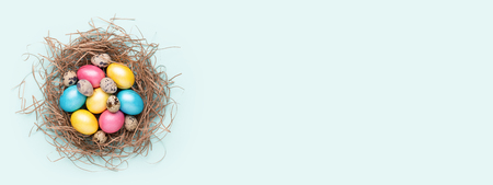 Colorful Easter eggs in nest on turquoise background. Top view, copy spase, minimal styled banner for website.