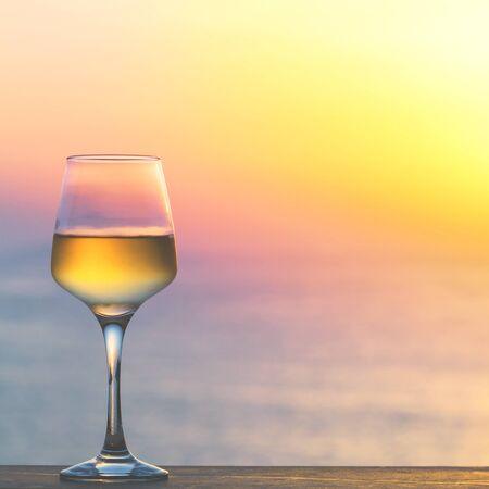 杯反对日落的白葡萄酒。美好的夏天晚上海视图。