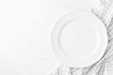 Weißer leerer Teller auf karierter Serviette auf weißem Holztisch. Draufsicht des leeren Tellers. Standard-Bild