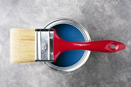 Can of classic blue paint with red brush on gray background. Top view. Reklamní fotografie - 137323468