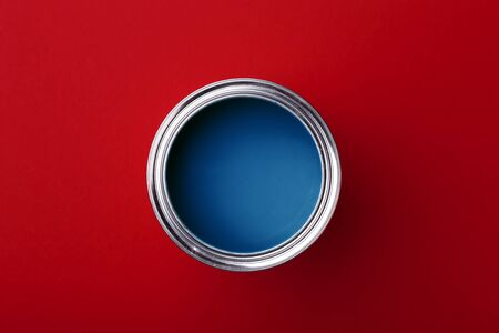 Can of classic blue paint on dark red background. Top view, color of year. Reklamní fotografie